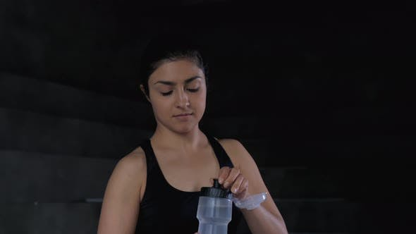 Close up shot of beautiful Indian sportswoman standing in gym and drinking water from bottle