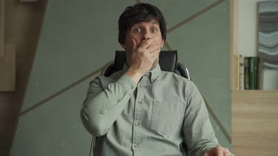 Young Man with a Surprised Expression is Sitting in a Chair in the Office