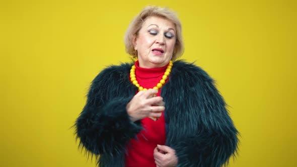 Thumbnail for Zuversichtlich Modische Senior Frau sprüht Parfüm in Zeitlupe