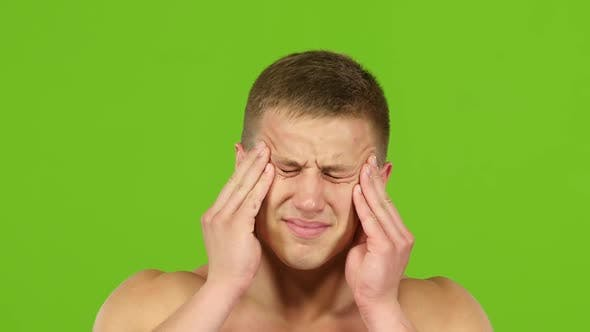 Cover Image for Man with Headache Is Massages Temples Hands, Green Screen. Closeup