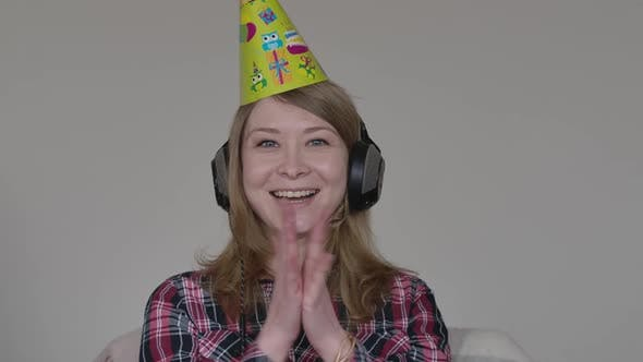 Thumbnail for Portrait of Cheerful Woman in Party Hat and Headphones Rejoicing. Young Joyful Girl Clapping Hands