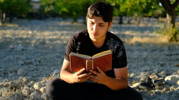 Man Reading Quran Outdoors