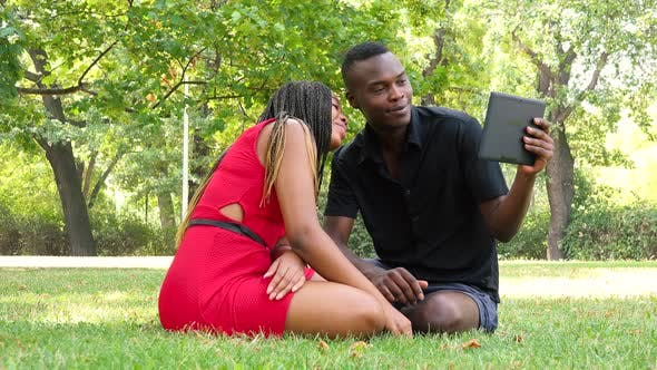 Thumbnail for A Black Man and a Black Woman Sit on Grass in a Park and Talk To Somebody on a Tablet
