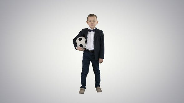 Thumbnail for Happy young school boy holding a football on gradient background