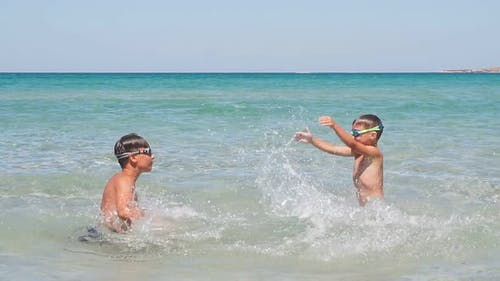 Children, Two Brothers Swim Happily Play, Splash on a Sunny Day in the Azure Sea, Enjoying a Family
