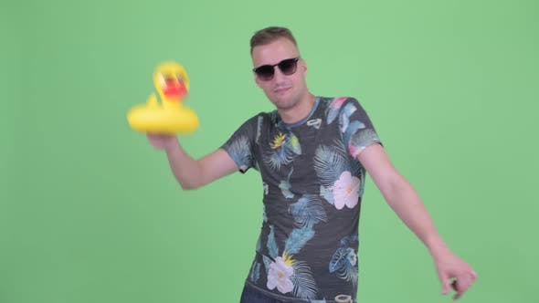 Thumbnail for Happy Handsome Man with Sunglasses Dancing with Inflatable Duck