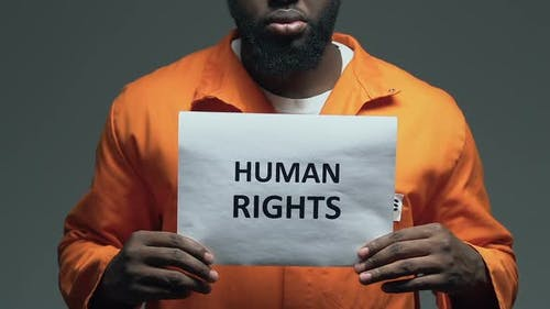 Human Rights Phrase on Cardboard in Hands of African-American Prisoner