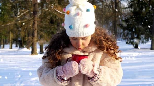 Thumbnail for Kleines Mädchen mit Tasse heißem Tee im Winter Park