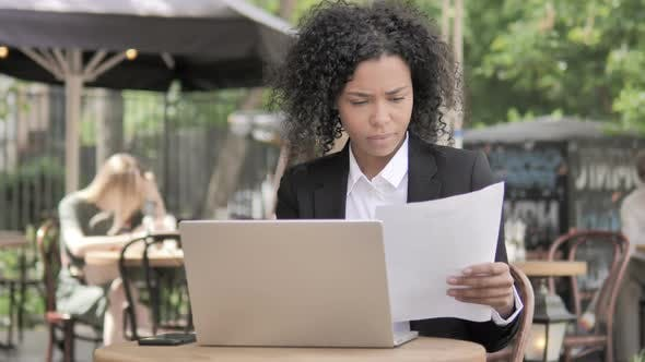 Thumbnail for African Businesswoman Reading Contract and Using Laptop in Outdoor Cafe