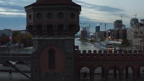 Medium Shot of Oberbaum Bridge Tower in Berlin, Germany Rising Up Revealing Cityscape Skyline with