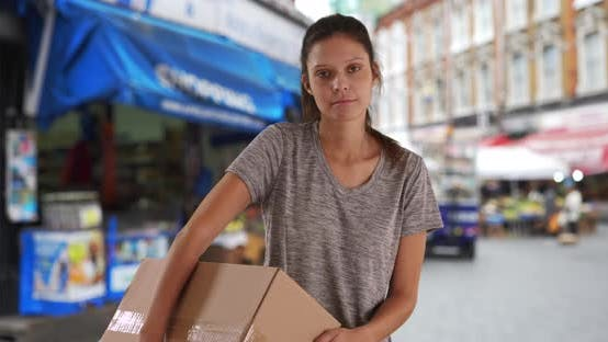 Thumbnail for Somber young woman in England carrying shipping box on street