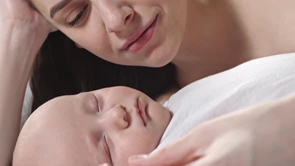 Cover Image for Loving Mother Kissing Sleeping Infant