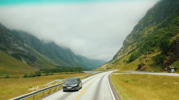 Cover Image for Scenic Road Among the Mountains in Norway. View From the Window of a Traveling Car