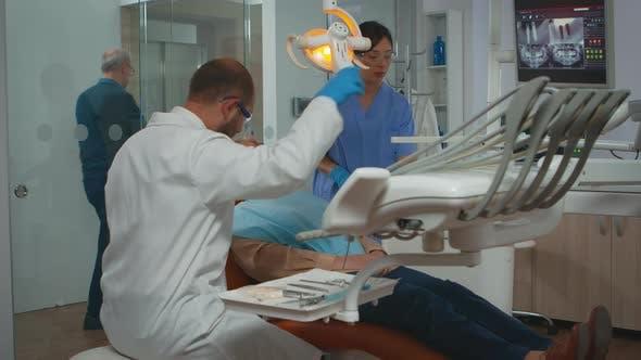 Thumbnail for Dentist Technician Preparing for Surgery Lighting the Lamp