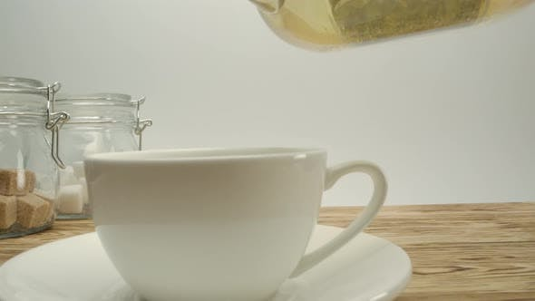 Pouring White Authentic Tea Into Classical White Cup on Wooden Table