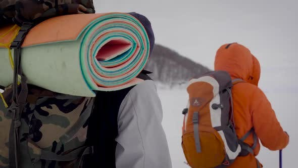 Thumbnail for Rear View Shot of Two Man Trekking in Winter with Big Backpacks. Guys Using Ski Poles To Walk on