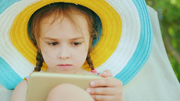 Thumbnail for A Cute Little Girl in a Large Multi-colored Hat in a Bathing Suit Is Sitting on a Lounger and
