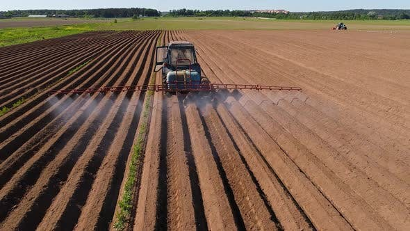 Cover Image for Farmer on a Tractor Sprays Plowed Fields with Fertilizers and Chemicals
