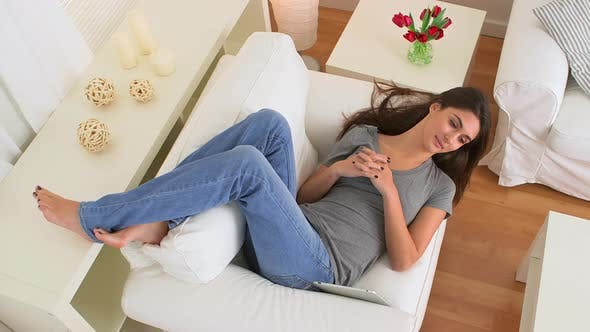 Thumbnail for Happy woman talking and smiling while lying on couch