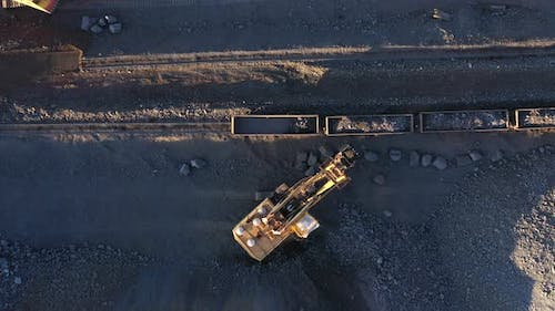 Excavator Loads Ore Into Freight Cars