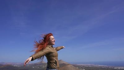 Woman Tourist Admires View From Mountain Top
