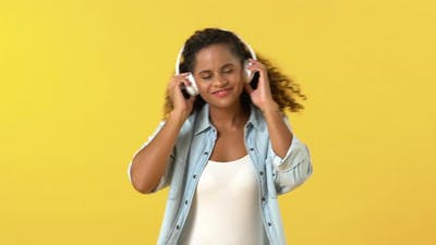 African American woman touching headphones while listening to music and dancing