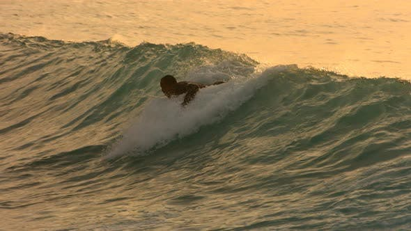 Surfer paddles into wave in late afternoon light, slow motion
