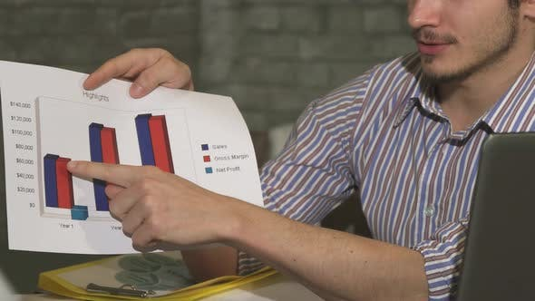 Thumbnail for Cropped Shot of a Businessman Showing Printed Diagrams on a Business Meeting