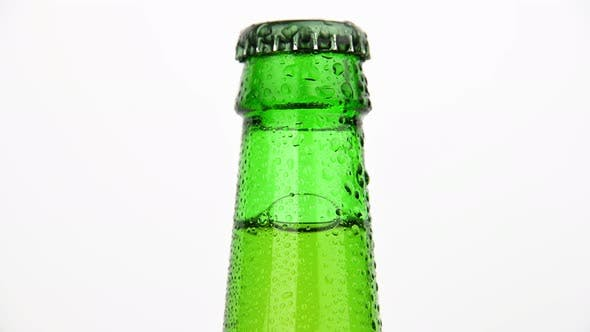 Thumbnail for Green glass bottle of beer frosty with water drops rotating over white