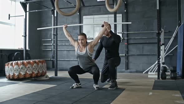 Thumbnail for Personal Trainer Helping Woman Doing Barbell Squats