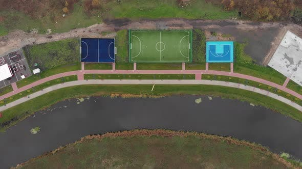 Recreation area near river with sports, football and basketball fields, cycling and pedestrian path
