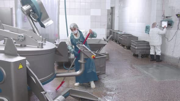 Worker Washes the Equipment with Water From a Hose at the Enterprise. Sanitary Cleaning of Sausage