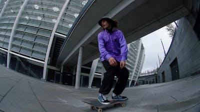 Sporty Man Jumping on Skateboard Outside