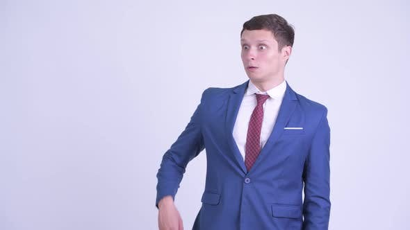Young Handsome Businessman Looking Shocked