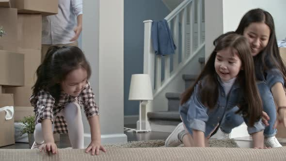 Thumbnail for Mother and Daughters Unrolling Carpet in New House
