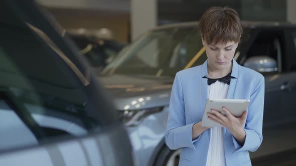 Thumbnail for Portrait of Confident Pretty Woman in Formal Wear Using Her Tablet Checking Cars in Motor Show. Lady