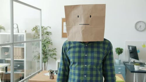 Portrait of Unhappy Guy Wearing Paper Bag with Emoji Standing at Work Shaking Head and Gesturing