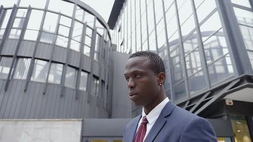 young black businessman in the street looks up,thinking future