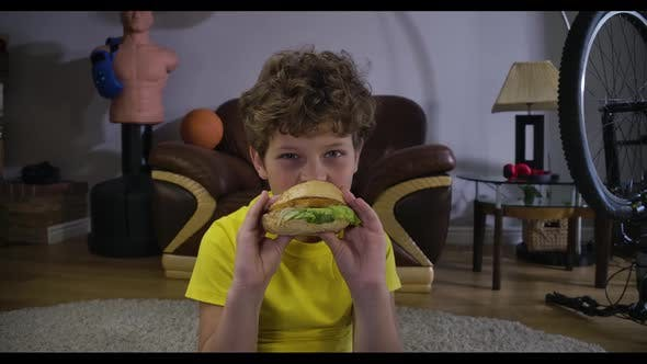 Thumbnail for Portrait of Caucasian Boy Watching TV and Eating Hamburger. Cute Curly-haired Teenager with Junk