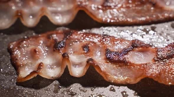 Pieces of Bacon Are Fried in a Pan. The Concept of Fatty and Junk Food, a Source of Trans Fats