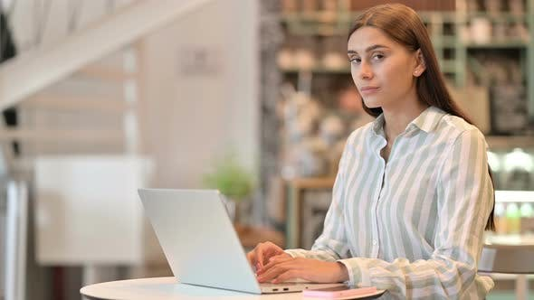 Smiling Young Latin Woman with Laptop Pointing at the Camera