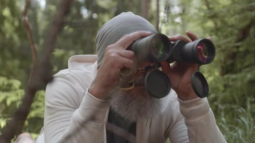 Aged Bird Watcher Using Binoculars