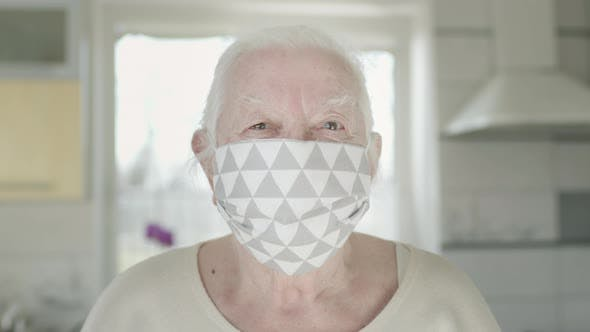Portrait Of Old Woman In Medical Mask. Woman Protects Herself From Infections In Pandemic