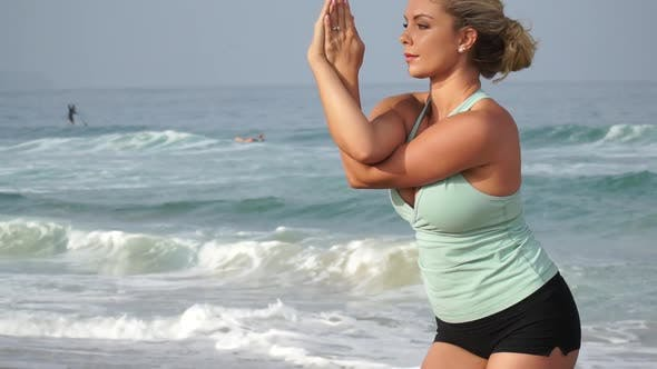 A young attractive woman doing yoga on the beach.