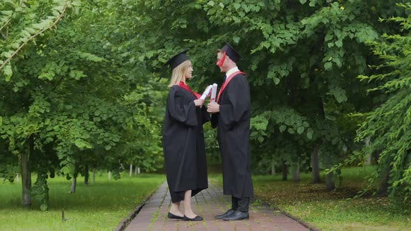 Thumbnail for Windy Weather Pair of Graduates Standing in Park With Diplomas Wind of Change