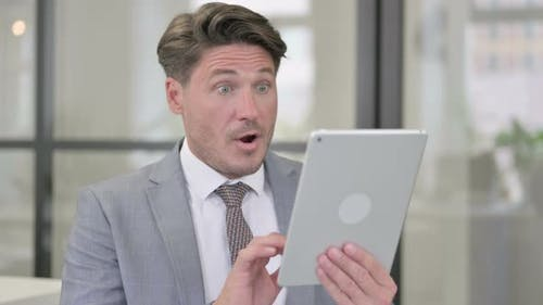 Middle Aged Man Celebrating on Tablet in Office