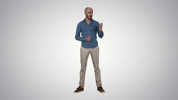 Thumbnail for Arabic Young Man in Shirt Talking Presenting Something and Pointing To the Side on Gradient