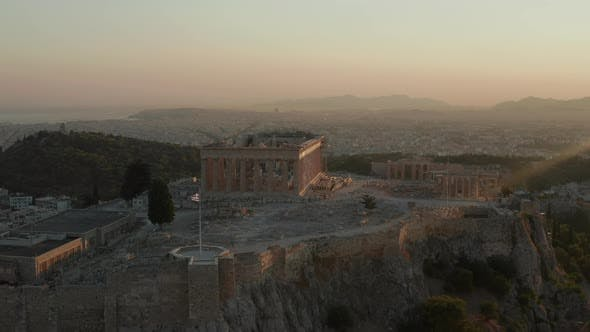 Aerial Flight Towards Acropolis of Athens with Greek Flag Waving in Beautiful Golden Hour Sunset
