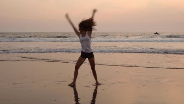 Thumbnail for Young Sportive Woman Doing Cartwheels on Ocean Beach at Sunset