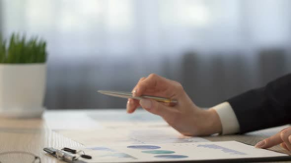 Cover Image for Financial Analyst Comparing Company Statistics and Making Notes on Graphs